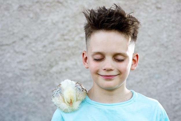 De jongen in een blauwe t-shirt met een pluizige kip sloot zijn ogen en droomt op een vage achtergrond.