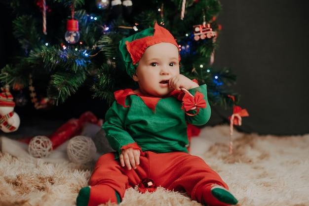 De jongen in een elfkostuum zit onder een kerstboom met een lolly