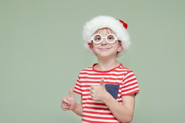 De jongen in en kerstmanhoed en glazen die beduimelt omhoog glimlachen tonen. portret