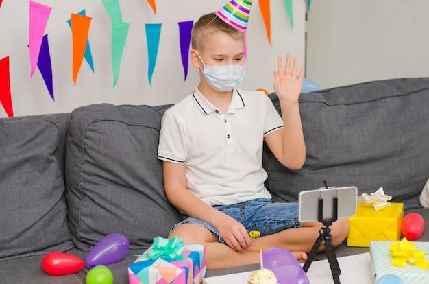 De jongen in geneeskunde gezichtsmasker viert verjaardag door videogesprek aan telefoon