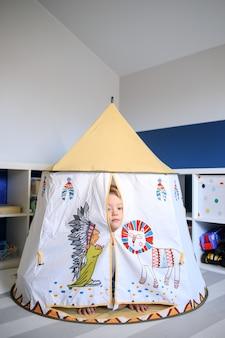 De jongen in het midden van de speelkamer bevindt zich in een speelgoedhuis.
