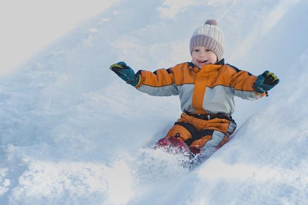 De jongen in hoed en oranje jumpsuit glijdt van sneeuwdia op rug. portret. detailopname.