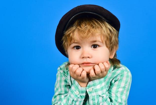 De jongen in overhemd houdt gezicht op handen. modieus klein kind in pet. retro stijl. knappe jongen in hoed.