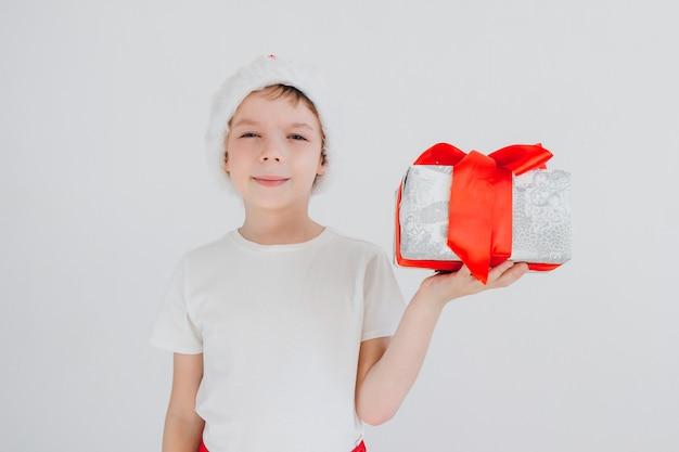 De jongen in rode kerstmuts houden geschenkdoos