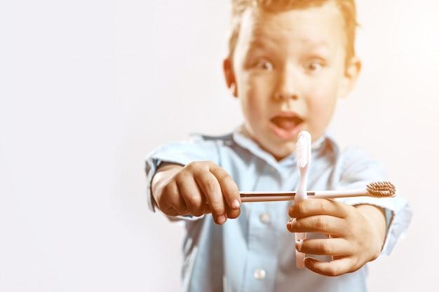 De jongen in tandenborstels van een de blauwe overhemdsholding en verheugt zich