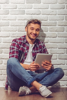 De jongen in vrijetijdskleding en pet gebruikt een digitale tablet.