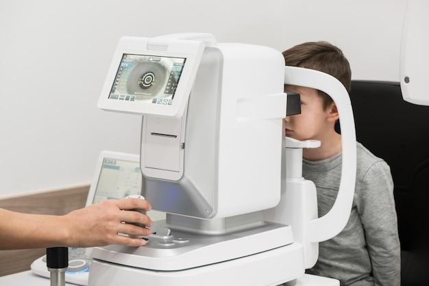 De jongen is de patiënt bij de receptie bij de arts oogarts diagnostische oogheelkundige apparatuur