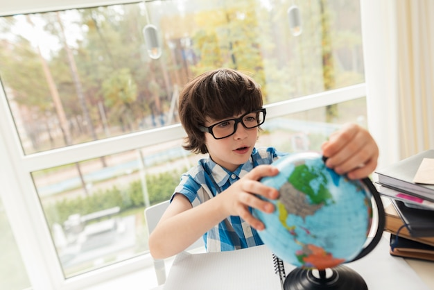 De jongen kijkt thuis naar de wereld.
