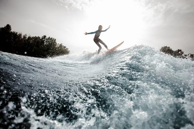 De jongen kleedde zich in het zwarte en blauwe zwempak surfen die omhoog op oranje raad tegen de zon springen