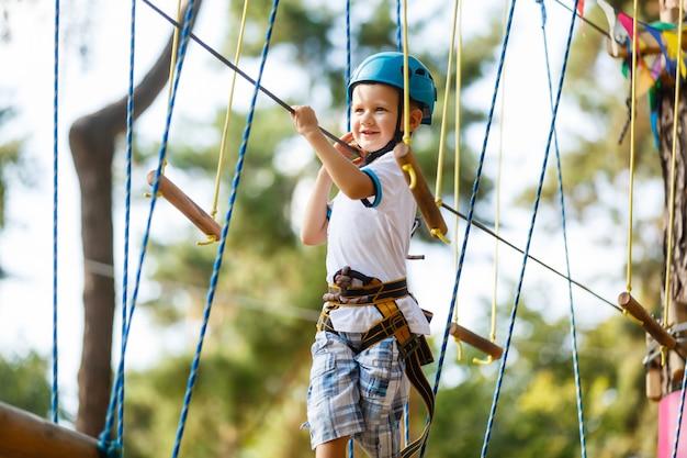 De jongen klimt een touwpark
