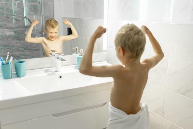 De jongen laat zijn biceps zien of trekt een gezicht voor de badkamerspiegel