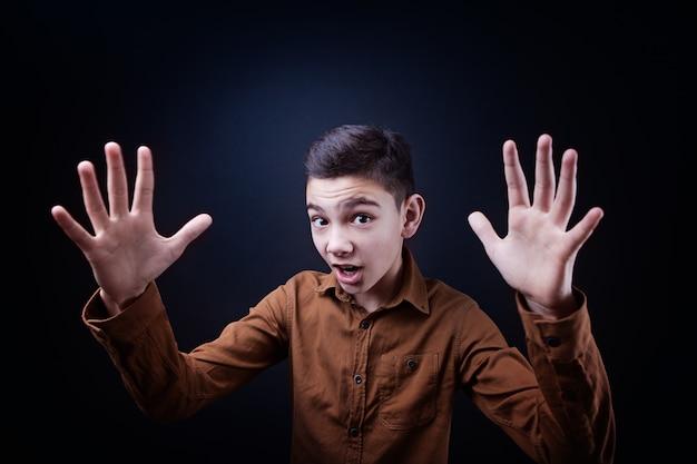 De jongen laat zijn handen iets groots zien, spreidt zijn handen in de zijkanten