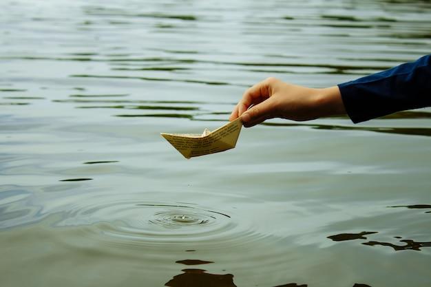 De jongen lanceert een boot op een waterclose-up