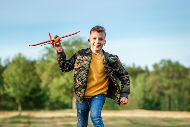 De jongen lanceert een speelgoedvliegtuig.