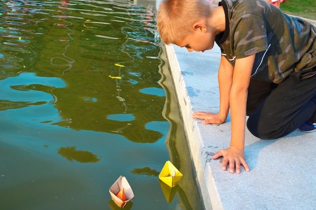 De jongen lanceert papierkleurige boten in de fontein.