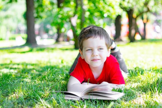 De jongen ligt op het gras en leest een boek. lezen in de natuur.