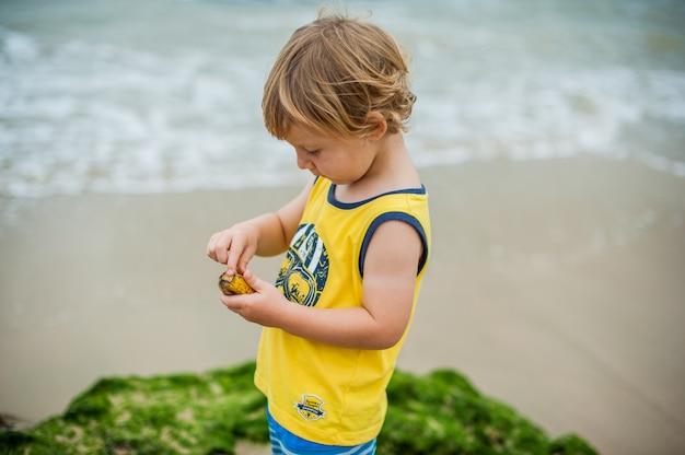 De jongen maakt een banaan schoon