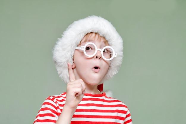 De jongen met een bril en een kerstmuts dreigt met zijn vinger. portret