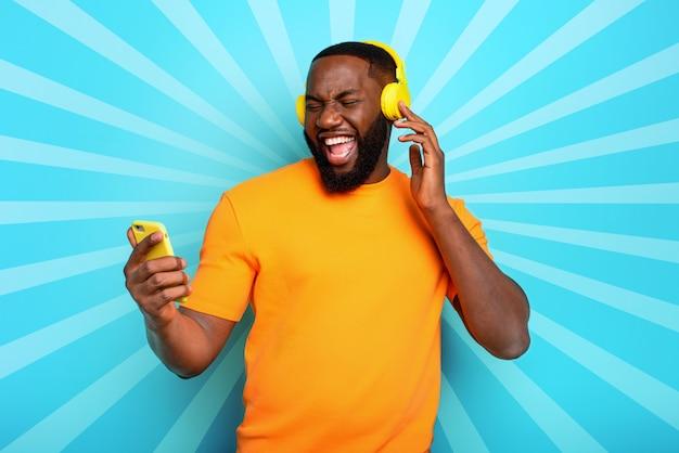 De jongen met gele hoofdtelefoon luistert naar muziek en danst op cyaanachtergrond. emotionele en energetische expressie