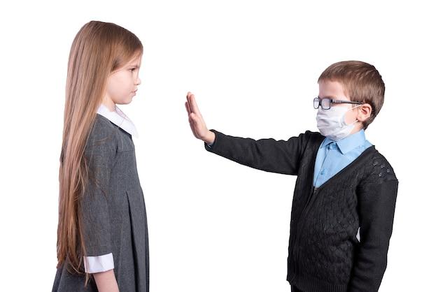 De jongen met het masker vraagt om sociale afstand te bewaren tot het meisje zonder het masker. geïsoleerd op een witte achtergrond. hoge kwaliteit foto