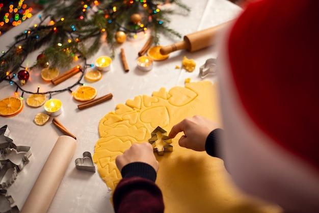 De jongen met kerstmishoed kookt koekjes