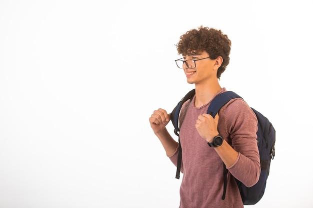 De jongen met krullend haar in een optische bril die zijn rugzak vasthoudt, is zelfverzekerd en gemotiveerd.