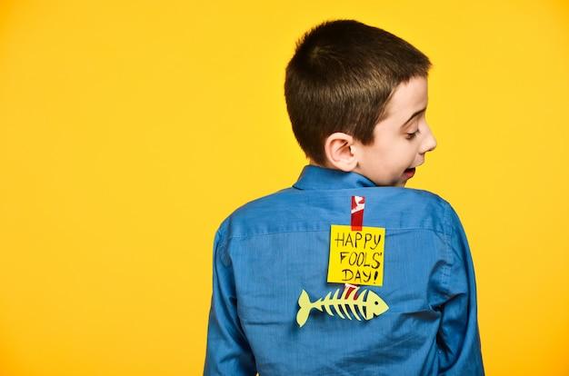 De jongen op een gele achtergrond in een blauw shirt met een vis gelijmd tape en een stuk papier op zijn rug