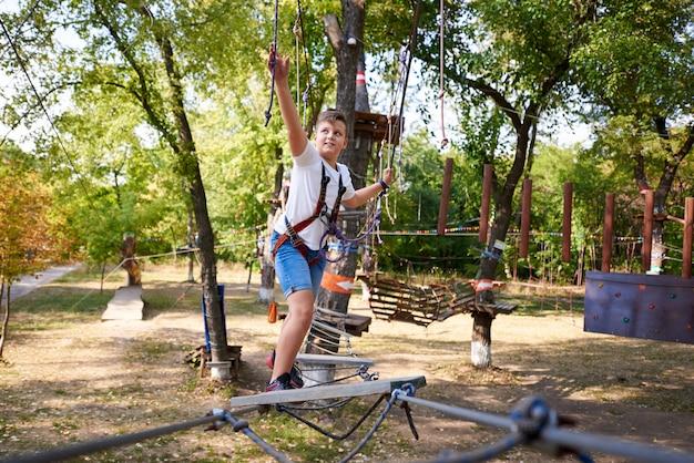 De jongen overwint het obstakel in het touwpark.