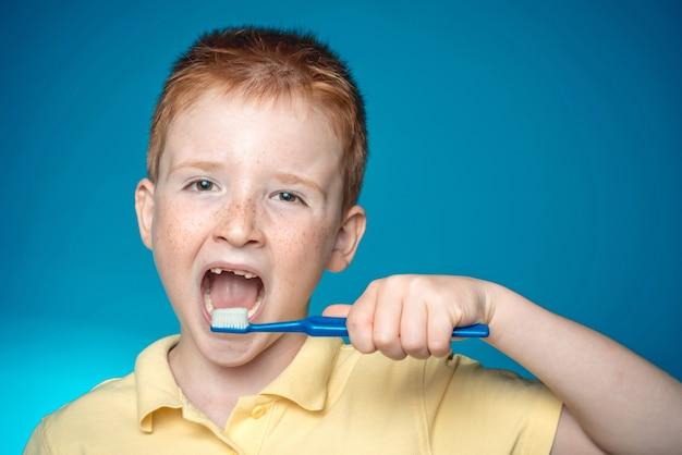 De jongen poetst zijn tanden. gelukkig kind jongen jongen tanden poetsen. smileyjongen zonder tanden met