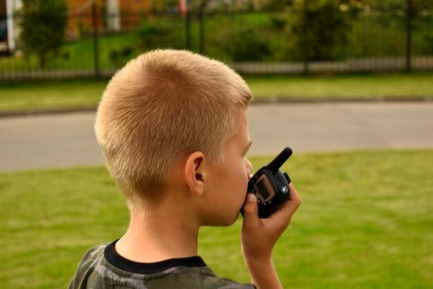 De jongen praat op de portofoon. jongensachtige oorlogsspellen.