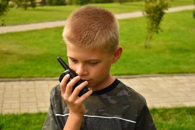 De jongen praat op de portofoon. kinderspeelgoed walkie-talkie in de hand.