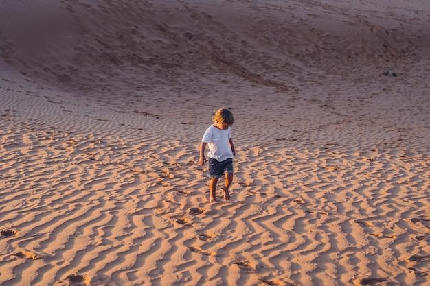 De jongen rent bij zonsopgang door de rode woestijn. reizen in een ophef met kinderen concept.