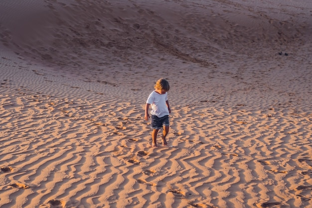 De jongen rent bij zonsopgang door de rode woestijn. reizen in een ophef met kinderen concept