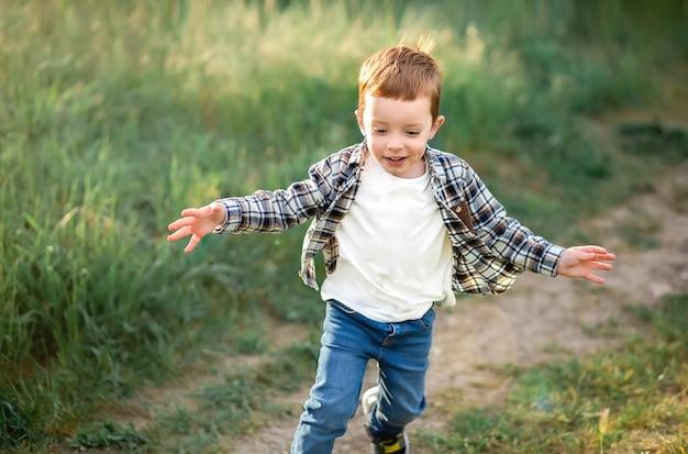 De jongen rent langs het pad op camera.