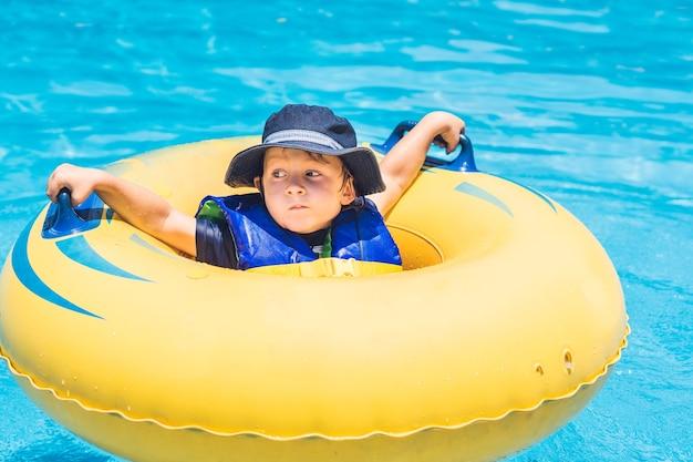 De jongen rijdt op een opblaasbare ring in een waterpark.