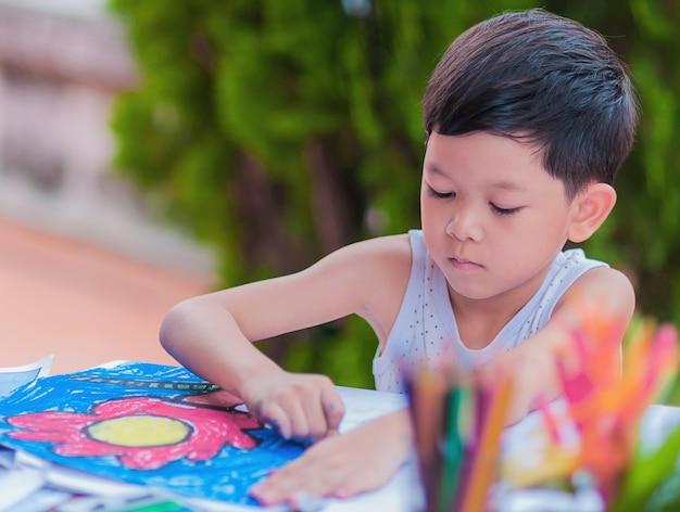 De jongen schildert kleurrijk beeld thuis.