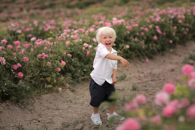De jongen schreeuwt en richt vinger op tot bloei komende bloemen