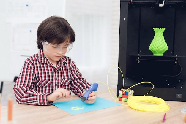 De jongen schrijft door 3d pen tijdens een les in klasse.