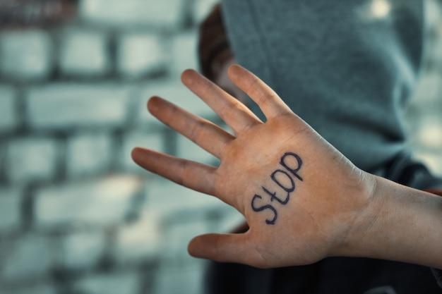 De jongen sluit zijn hand, geschreven op zijn hand stop, wreedheid tegen kinderen