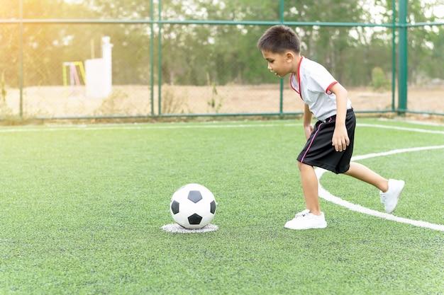 De jongen speelde van geluk op het voetbalveld voetbal.