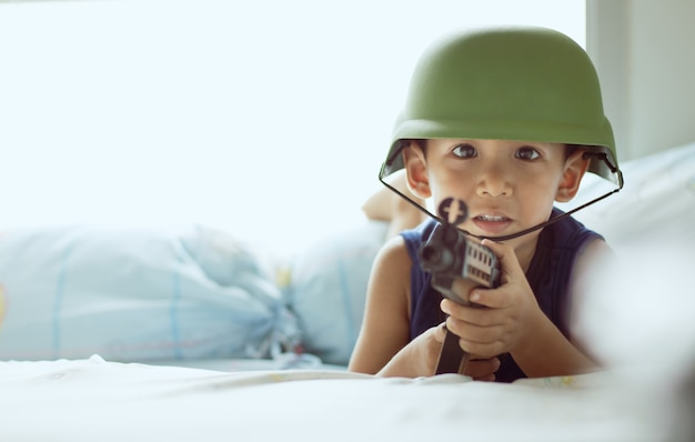 De jongen speelt de rol van soldaat, houdt een speelgoedgeweer vast, draagt een militaire hoed, speelt op het bed.