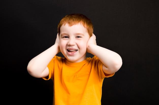De jongen speelt en bedekte zijn oren met zijn handen en wil niets horen