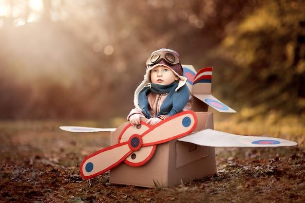 De jongen speelt in een vliegtuig gemaakt van een kartonnen doos en droomt ervan piloot te worden