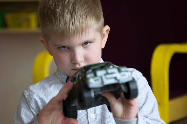 De jongen speelt met een groene tank. toekomstige militaire soldaat