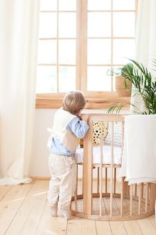 De jongen staat naast het bed in de kinderkamer en gluurt. de eenzame baby is in kleuterschool dichtbij de wieg. eenzaamheid. milieuvriendelijk kinderkamerdecor in de scandinavische stijl. de jongen is thuis.