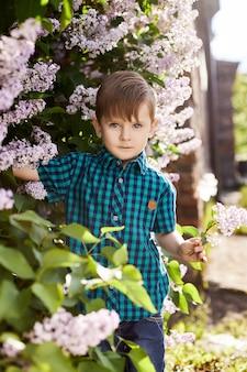 De jongen stelt in een lila struik in het voorjaar. romantisch portret van een kind in bloemen in het zonlicht