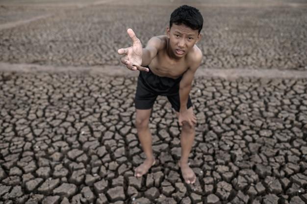 De jongen stond gebogen op zijn knieën en maakte een teken om regen, opwarming van de aarde en watercrisis te vragen.