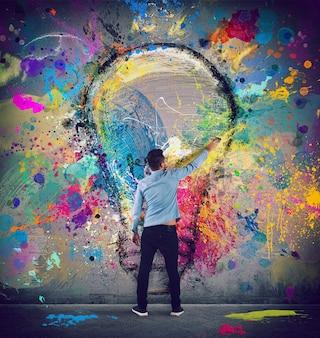 De jongen tekent met een penseel een abstracte grote gloeilamp. concept van innovatie en creativiteit