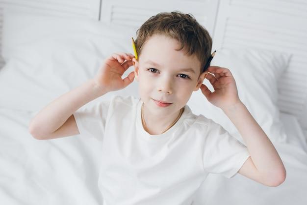 De jongen trekt met kleurrijke potloden zittend op het bed