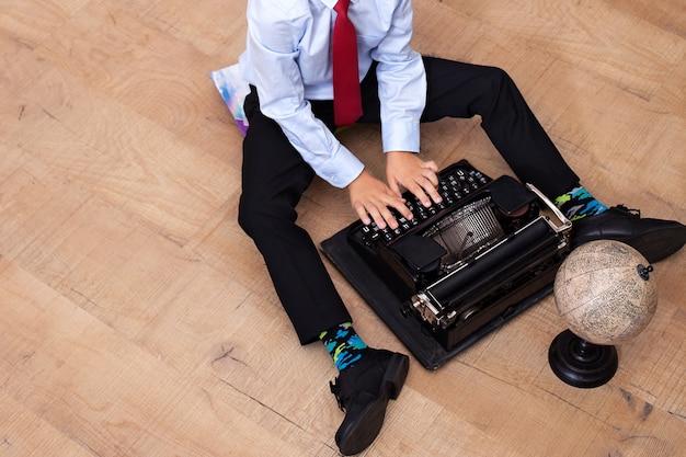 De jongen typt op een oude typemachine. schooljongen met een vintage machine. de jongen zit op de grond en houdt een retro-schrijfmachine vast. close-up van hand van jongen als directeur die typemachine gebruiken. school-